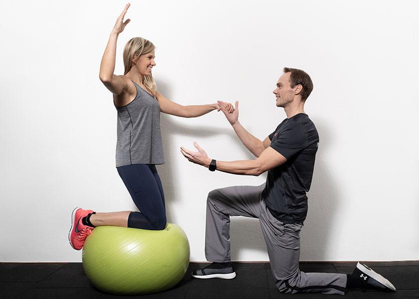Der Trainer unterstützt bei einer Balance Übung