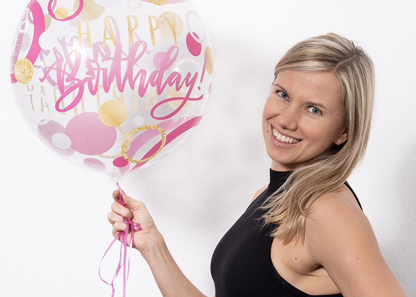 Die Trainerin hat einen Geburtstags Luftballon in der Hand