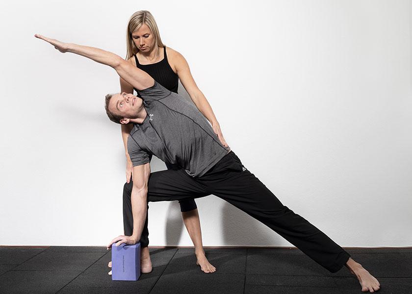 Die Trainerin hilft bei der Yogapose