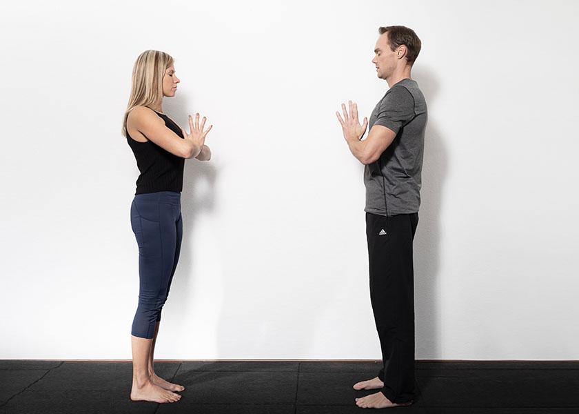 Die Trainer begrüßen sich in einer Yoga Pose