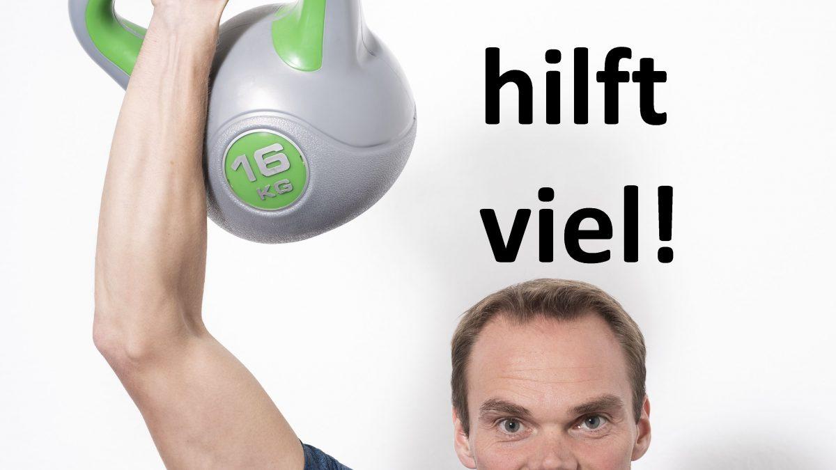 Trainer hebt eine Kettlebell über den Kopf und sagt viel hilft viel
