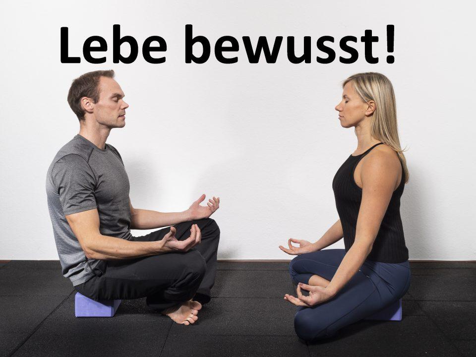 Zwei Trainer begrüßen sich bei einer Yoga Stunde im Schneidersitz