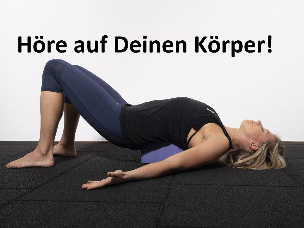 Die Trainerin liegt auf einem Yogablock und dehnt die Brustmuskulatur