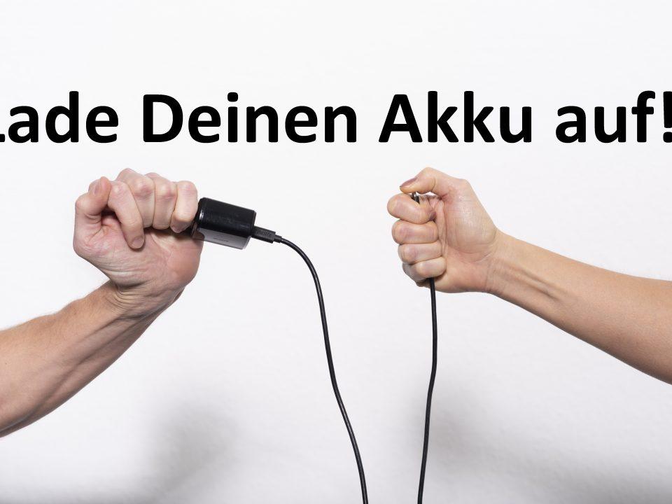 Zwei Hände sind über ein Ladekabel verbunden und laden sich gegenseitig auf