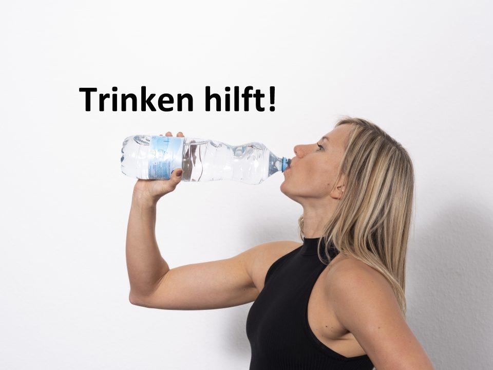 Trainerin trinkt aus einer Wasserflasche